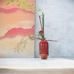 The AKA Tall Vase, a hand-thrown ceramic vase with a multi-level finish of black and bright red glazes This vase is decorated with antique gold and red chrysanthemum flowers. Available now at k-3.com